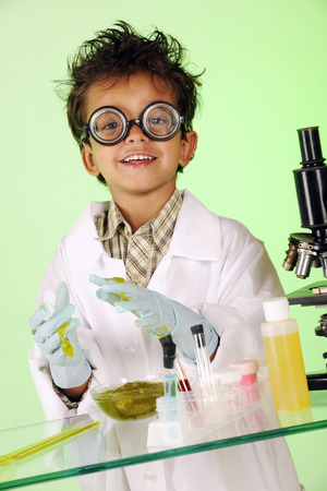 wild hair: A preschooler with wild hair in lab coat, coke-bottle glasses and gloves, happily working with slipery green slime on a glass table with lab equipment.