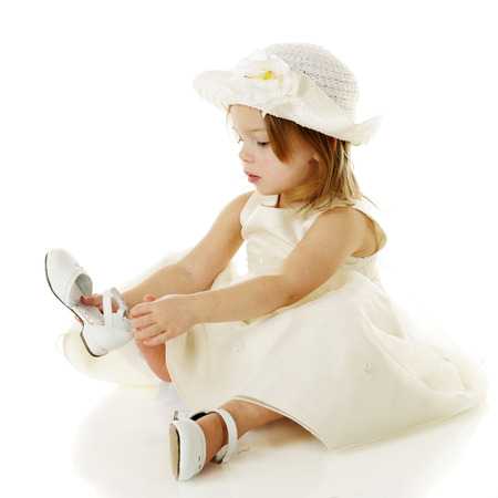 dressed up: A beautiful, dressed up preschooler putting on her own white shoes.  On a white background.