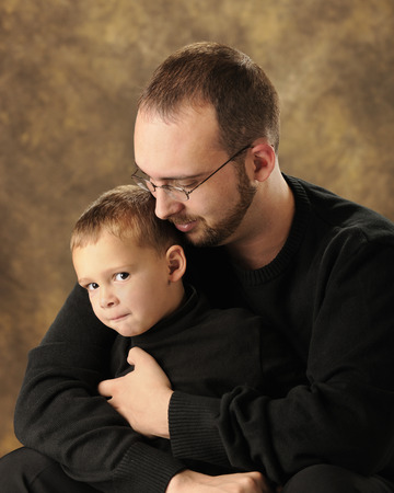 snuggling: Close up image of a father snuggling with his young son who is grinning at the viewer from the corner of his eye.  Both are dressed in black.