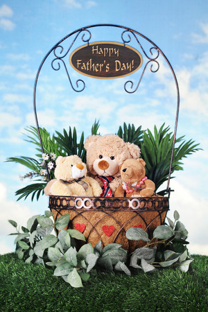 knoll: Toy bears -- father, son and daughter snuggled together within a foliage-filled wire basket on a grassy knoll with sky in the background..  A Happy Fathers Day sign dangles from the handle.