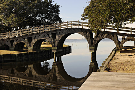 foot bridge: A wooden foot bridge with its reflection over a still waterway. Stock Photo