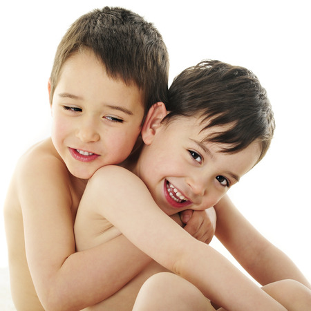 bare chested: Two handsome preschool brothers having fun hugging each other.  On a white background. Stock Photo