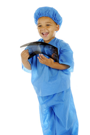 scrub cap: A biracial preschool surgeon delighted with the x-ray of a hand that he holds.  On a white background.
