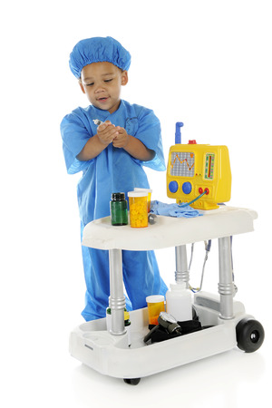 emergency cart: An adorable preschool doctor in scrubs, drawing up medicine from a bottle on his emergency cart.  On a white background.