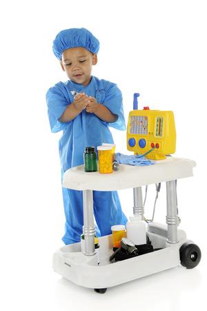 """preescolar: Un preescolar """"doctor"""" adorable en matorrales, la elaboración de la medicina de una botella en su carro de emergencia. Sobre un fondo blanco."""