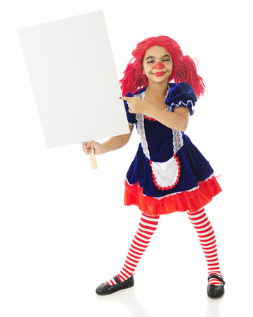 A young elementary rag doll holding a blank sign (for your text) and happily pointing to it.  On a white background. photo