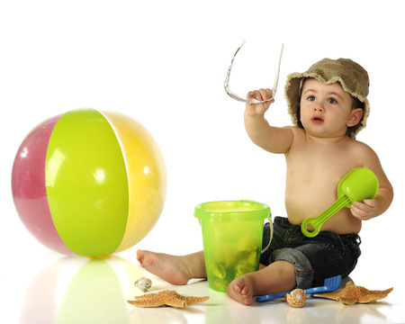 beach toys: An adorable baby boy in rolled up jeans and hat handing off his sunglasses as he sits among sea shells and beach toys.  Isolated on white. Stock Photo
