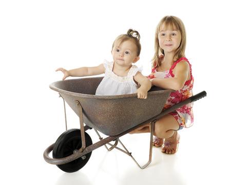 en cuclillas: Dos hermanas con una carretilla - el bebé que montan en el interior, la hermana elemental feliz en cuclillas detrás. Sobre un fondo blanco.