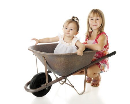 squatting: Two sisters with a wheelbarrow -- the baby riding inside, the elementary sister happily squatting behind.  On a white background.