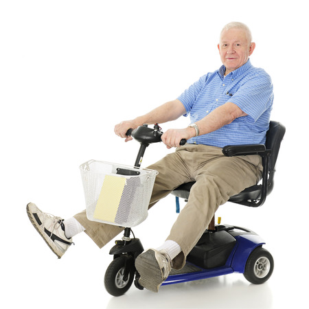 A senior man delightedly driving his electric scooter.  Motion blur on wheels.  On a white background. photo