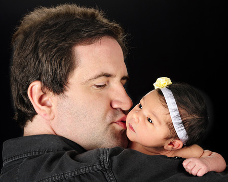 black newborn: A Daddy holding and kissing his newborn daughter.  On a black background.