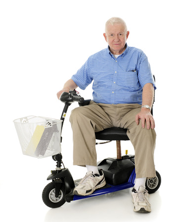 looking at viewer: A senior man happily looking at the viewer from his electric scooter.  On a white background. Stock Photo