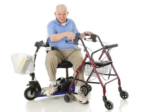 scooter: Un hombre mayor que se sienta de lado en su scooter mientras se apoya en las asas de su rueda andador. Sobre un fondo blanco.