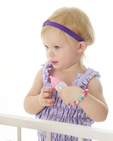 Een schattige 2-jarige staande wieg-kant klaar om haar poppen te voeden met een babyfles. Op een witte achtergrond.
