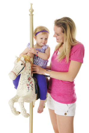 antiqued: An adorable 2-year-old happily riding an antiqued carousel horse with her mommy by her side.  On a white background.
