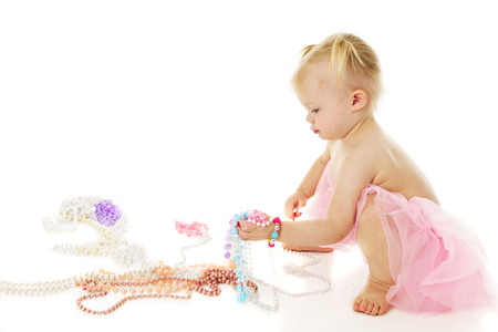 girl squatting: An adorable little girl squatting as she picks up a fistful of colorful pearls.  On a white background with plenty of space for your text above the multiple necklaces on the floor.