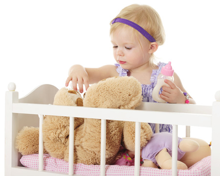 olds: An adorable 2-year-old checking on the Teddy bear in her doll crib.  She olds a full baby bottle in one hand.  On a white background.