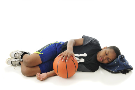 duffle: A preteen athlete asleep with his head on his gym bag and hand resting on his basketball.  On a white background with space over the sleeper for your text. Stock Photo