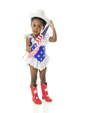 2 year old: An adorable 2 year old in a star spangled majorette outfit adjusting her hat as she holds an American flag.  On a white background.