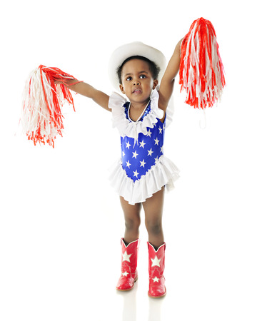 upraised: An adorable two year old celebrating the USA with upraised pompoms, while dressed in her red, white and blue star-studded outfit.  On a white background.