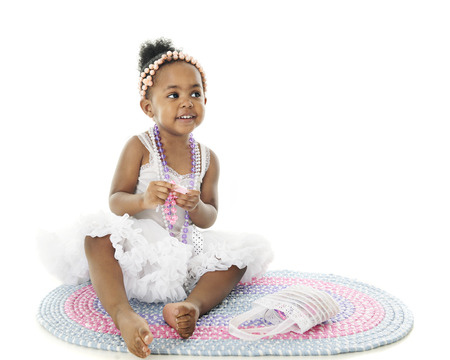 petticoat: An adorable 2 year old sitting pretty barefoot in her petticoat and adorned with beads.  She sits on a pastel rag rug.  On a white background with space on the right for your text. Stock Photo