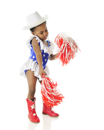 pom poms: An adorable two year old shaking her pom poms while wearing a red, white and blue star studded outfit. On a white background. Stock Photo