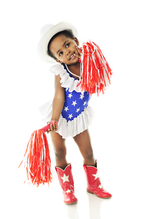 An adorable two year old in a star-studded red, white and blue majorette outfitt.  She wears a white cowgirl hat and holds two red and white pompoms.  On a white background. Stock Photo
