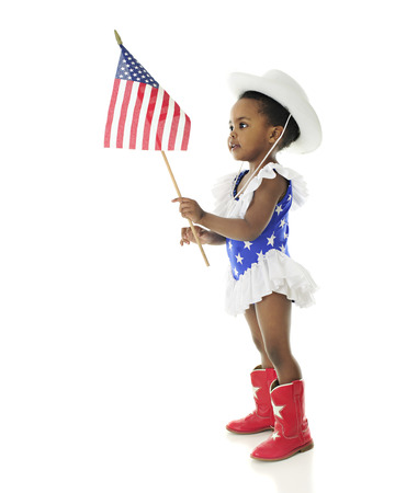 patriotism: An adorable African American girl looking at the American flag she holds while wearing a red, white and blue majorette outfit.  On a white background. Stock Photo