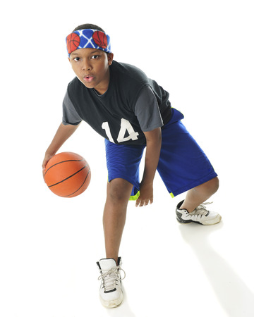 tween: An African American tween basketball player actively dribbling his ball.  On a white background.