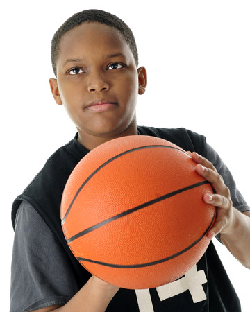 Close-up image of a preteen basketball player prepared to make a basket.  On a white background.