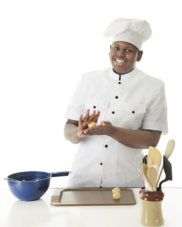 cookie sheet: A young chef smiling at the viewer as he hand rolls dough into balls before placing them on the cookie sheet.  On a white background with space on left for your text.