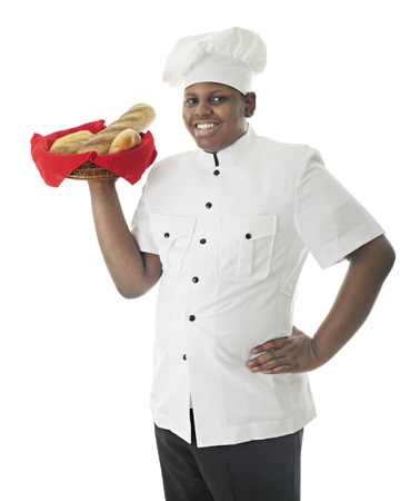A young African American chef carrying a variety basket of breads over his shoulder.  On a white background.