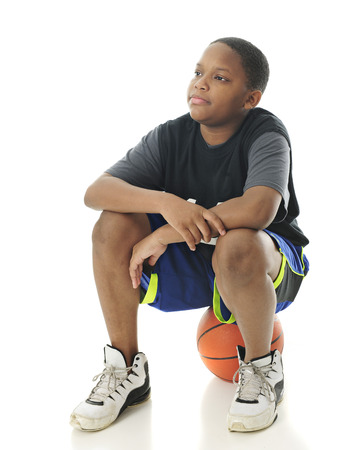 preteen: A preteen boy sitting on his basketball while looking for other players to show up.  On a white background.