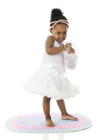ragazze a piedi nudi: Un adorabile di due anni cercando ritroso nel sottoveste e perle. Su uno sfondo bianco.