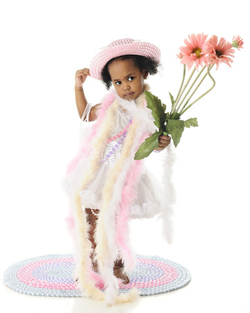 boas: An adorable barefoot two year old standing in pearls and boas.  She carries a small bouquet of tall pink flowers.  On a white background.
