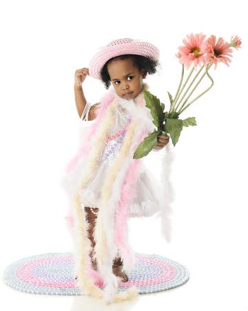 boas: Un adorabile a piedi nudi di due anni in piedi in perle e boa. Lei porta un piccolo bouquet di fiori rosa alti. Su uno sfondo bianco. Archivio Fotografico