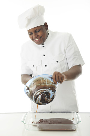 white backing: A young African American chef pouring chocolate batter from his mixing bowl to the backing dish.  On a white background. Stock Photo