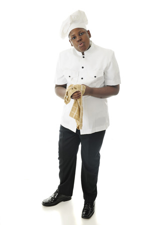 looking at viewer: A young African American chef, looking at the viewer tired and wiping his hands on a towel after a long, hot shift.  On a white background.