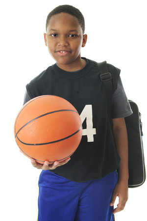A preteen athlete carrying his gym bag while holding out his basketball in an invitation to play.  On a white background. Imagens