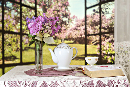 An opened Bible on a table set with a teapot, tea cup and bouquest of violate lilacs, all set before a window opened to a sunny field of lilacs bushes.  Shallow depth of field with focus on the Bible.