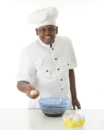 looking at viewer: A young chef looking at the viewer as he makes brownie batter with one egg in hand and an empty egg shell nearby.  On a white background. Stock Photo