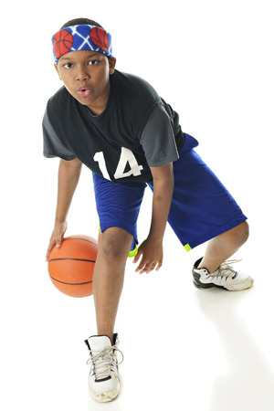 looking at viewer: Full length image of a preteen basketball player looking at the viewer as he dribbles between his legs.  On a white background.