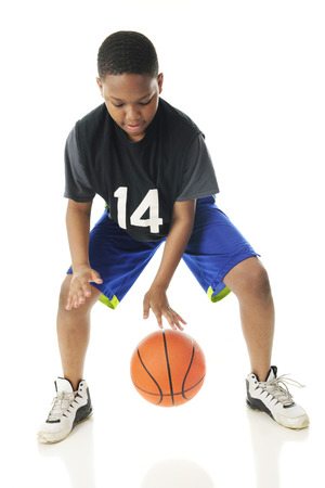 dribbling: A preteen athlete rappidly dribbling his basketball close to the floor.  Motion blur on hands and ball.  On a white background.