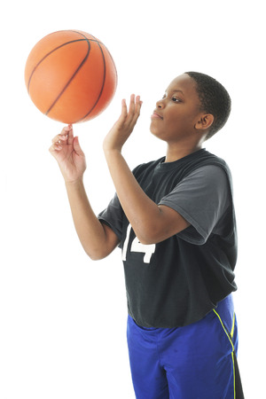preteen boys: A preteen boy successfully spinning a basketball on an index finger.  Motion blur on the ball.   On a white background. Stock Photo