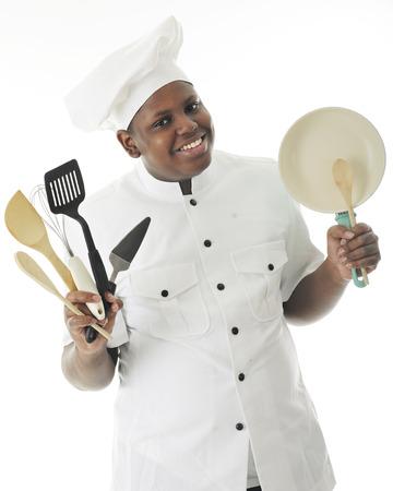 cocinero: Un joven afroamericano feliz mostrando algunos de sus utensilios y una pequeña sartén. Sobre un fondo blanco.
