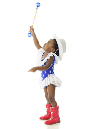 year profile: Profile of an adorable African American 2 year old wearing a wester patriotic outfit and stretching high with her baton.