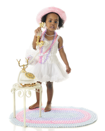 french fancy: An adorable 2 year old diva calling the viewer to her fancy French phone.  She wears a white slip and petticoat, and pastel hat and beads.  On a white background. Stock Photo