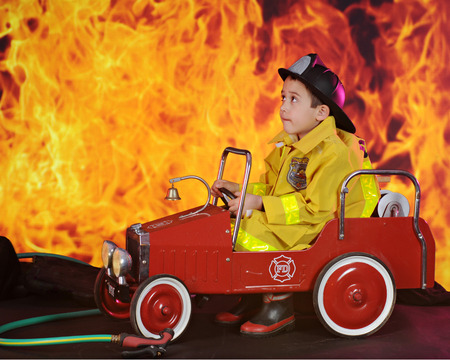he: An adorable preschool fireman looking worried as he drives his vintage fire truck to an inferno.