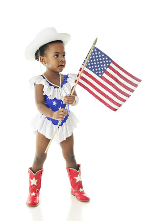 black cowgirl: An adorable African American two year old prepared to march in a parade in her western majorette outfit of star-studded red, white and blue and carrying an American flag.  On a white background.