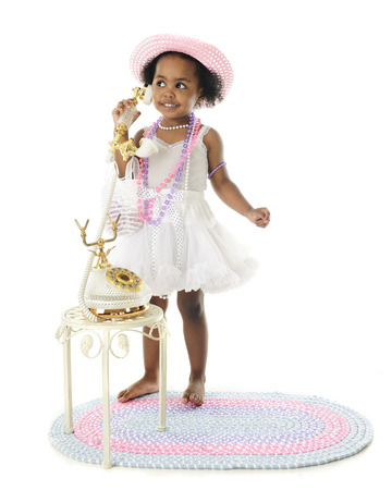 petticoat: An adorable two year old diva standing in her petticoat and pearls and chatting on a fancy French phone.  On a white background. Stock Photo